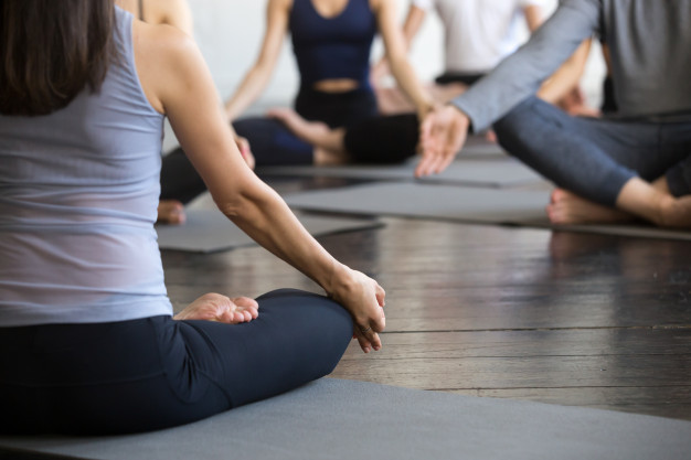 group-young-sporty-people-sitting-lotus-pose-closeup_1163-4127